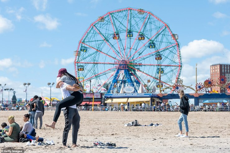 Brooklyn, New York: A couple embraced in front of the Wonder Wheel at Coney Island