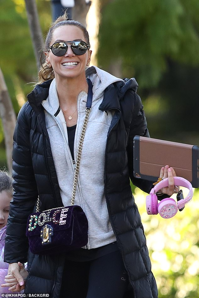 She's got her hands full! The multi-tasking mother carried a tablet and pink My Little Pony headphones, which presumably belonged to her daughter