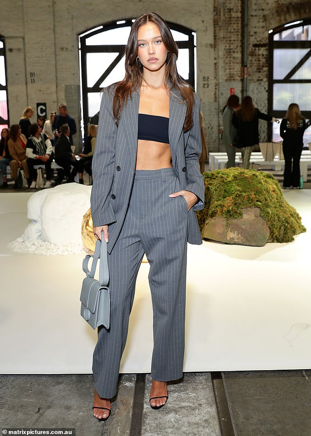 Crop queen: Model Isabelle Mathers also attending the fashion event who looked stylish in her ensemble.The brunette beauty wore an grey, oversized pin-stripped suit by Scanlan Theodore with a black bandeau crop top that drew attention to her washboard abs