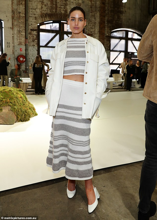Stylish: Tahnee Atkinson opted for a chic look in a grey and white knitted crop top and a matching midi-length skirt.The Australia's Next Top Model star, 29 capped off her look with a white coat over and matching sling back heels