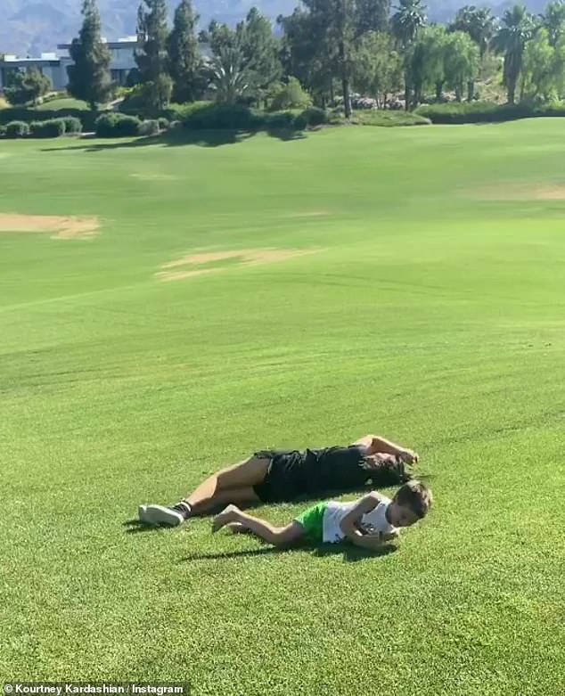 Blissful: Barker, 45, and the Poosh founder's little boy, Reign, appeared to be having the time of their lives as they lid down a water slide and rolled down a hill together