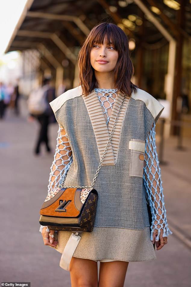 Details: She added a knitted vest-dress over the top, and carried a Louis Vuitton shoulder bag