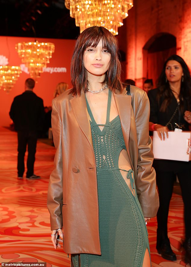 Lovely:She added a brown trench coach over the top,wore a silver choker, and opted for chunky, straightened hair and a soft makeup palette with a pale, pink lip