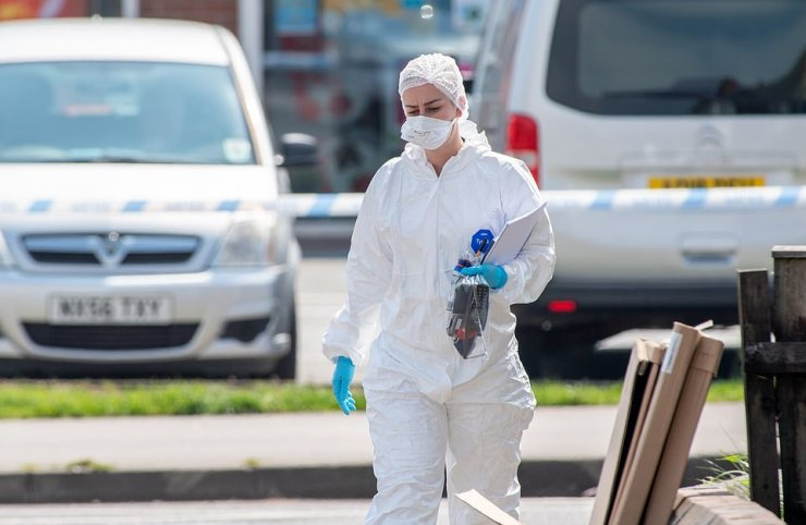 A forensic officer is seen clutching a bag of evidence at the scene of the double murder in Louth