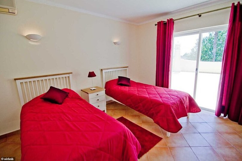 Colourful: One bedroom features two single beds with bright red covers and matching curtains