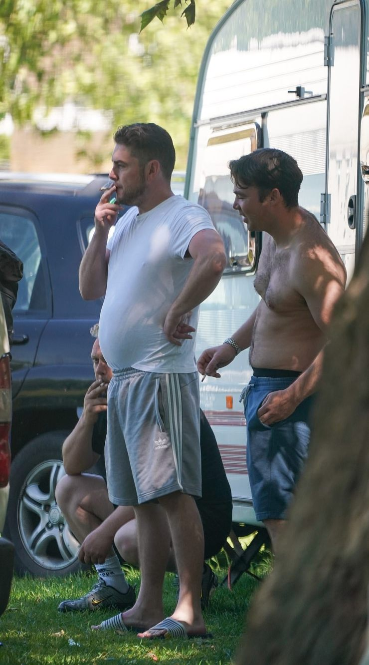 Three men enjoy a smoke as the pressure mounted following the group's arrival in the affluent park late last week