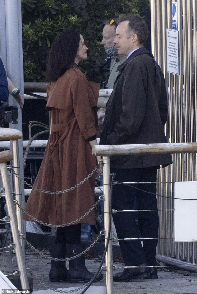 And, action! Eva Green cut a stylish figure in a bronze coat and a black turtleneck top as she filmed a mystery project with a male co-star near Tower Bridge, London, on Tuesday