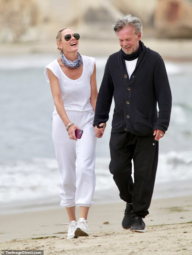 Romantic walks on the beach!Natasha certainly seemed smitten as she enjoyed a leisurely stroll with John on Saturday