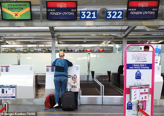 A woman with a child by a check-in desk at Pulkovo International Airport for a Wizz Air flight