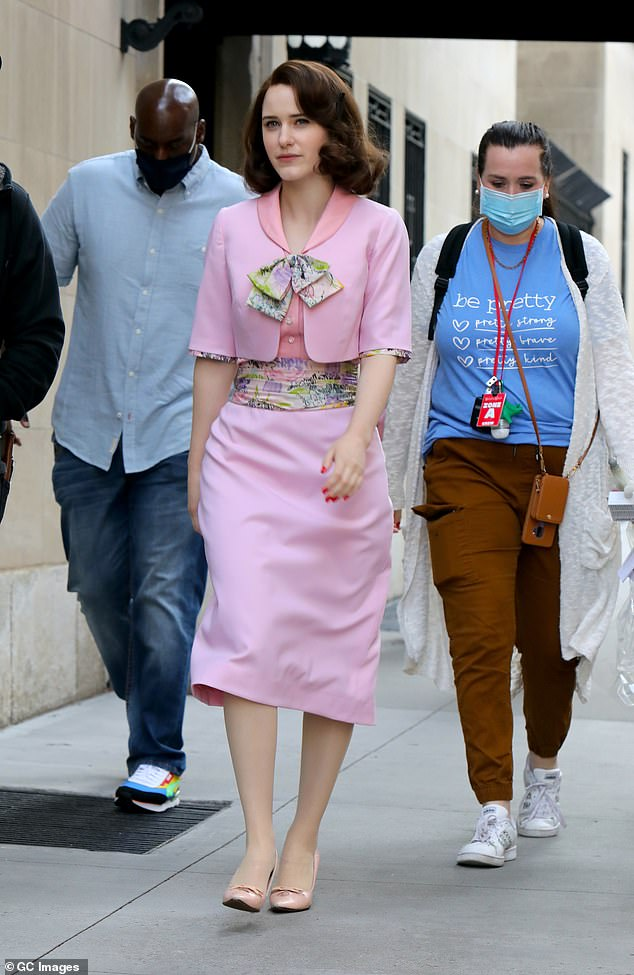 Chic fit: She embraced her onscreen character Mirium with a pink dress and floral belt cinched at the waist which she paired with a cropped cardigan, complete with floral trim and a bow