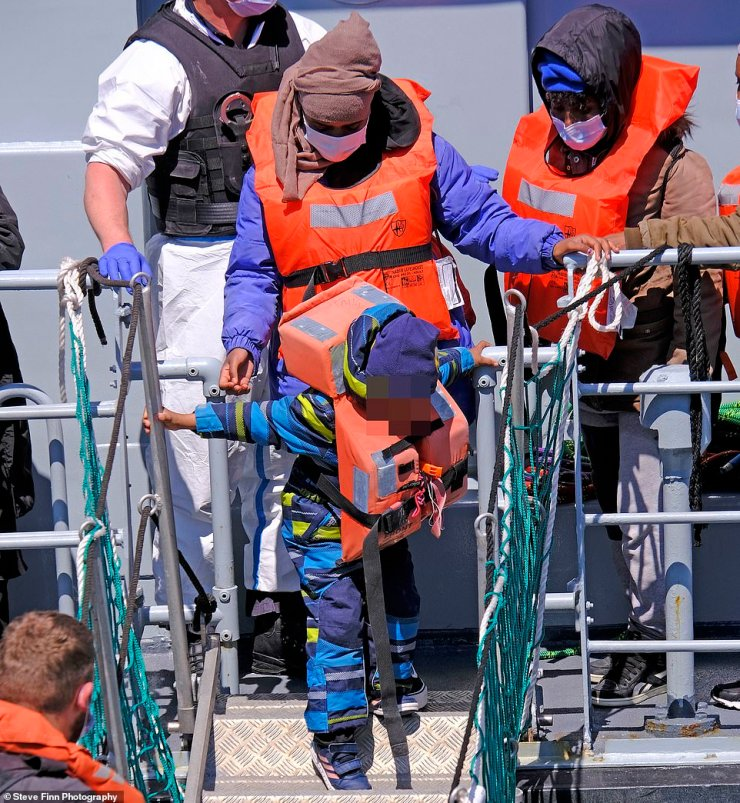 A child walks off a boat after an estimated 200 migrants were brought into Dover Marina in Kent yesterday
