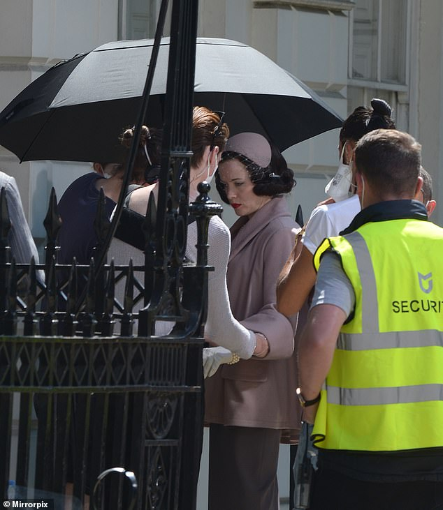 Sheltered:While in other images she was being shielded from the sun's rays with a large black umbrella by crew members as they filmed during the British heatwave
