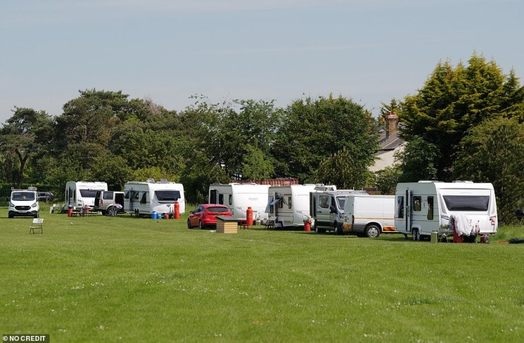 A row of caravans are seen stretched out along the grass in Dedworth. Officials were seen talking to travellers there