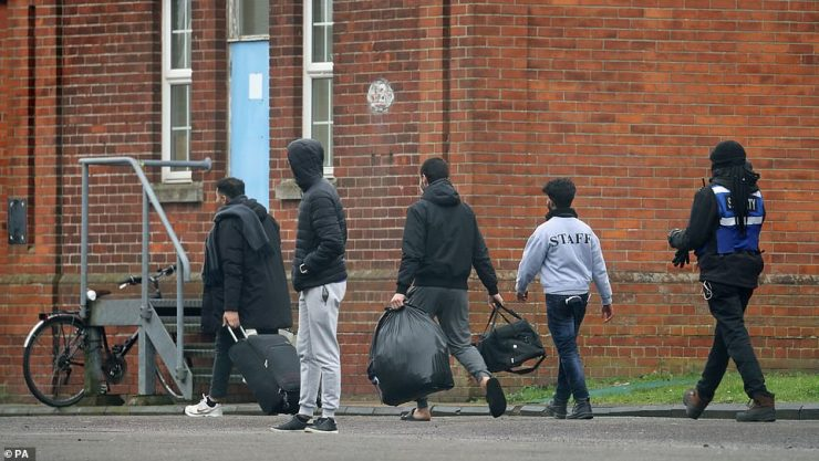 Two men leave Napier Barracks in February, which is being used by the government to house people seeking asylum in the UK