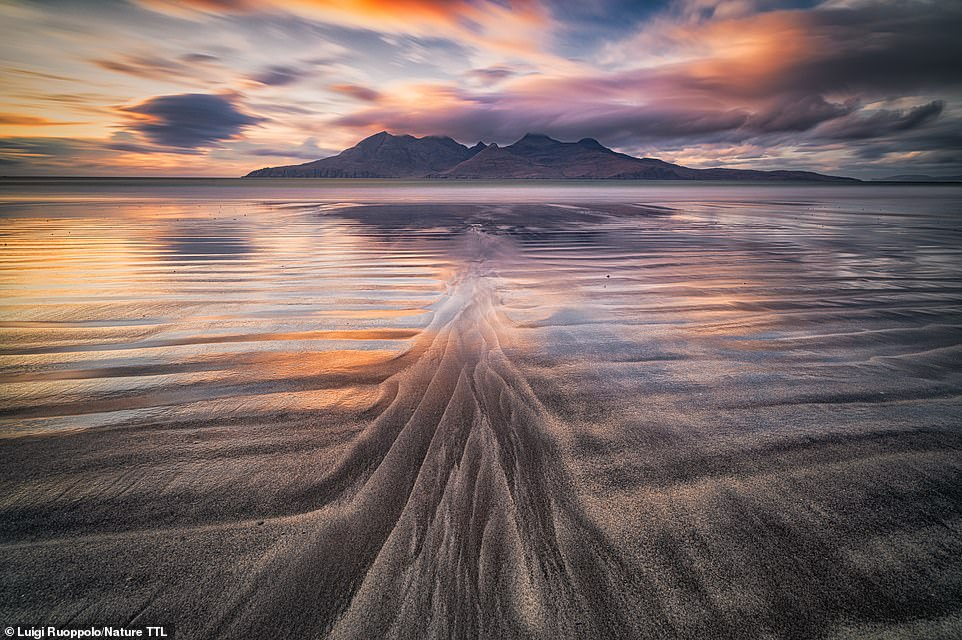 This spellbinding shot was taken at sunset byLuigi Ruoppolo on the Scottish island of Eigg. It shows the 'beautiful colours and stunning clouds moving over the mountains of Rum island'. He explains: 'I was quite far from the shoreline, following the patterns left in the sand by the tide and shooting at 90 seconds exposure to get as many reflections as possible.' The shot is highly commended in the landscapes category