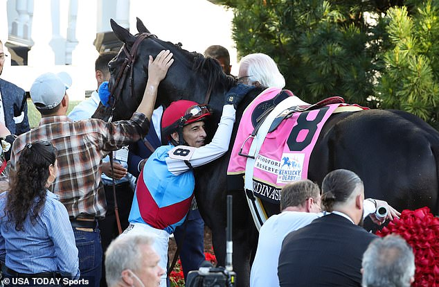 ohn Velazquez embraces Medina Spirit (8) in the winner's circle after the 147th running of the Kentucky Derby at Churchill Downs