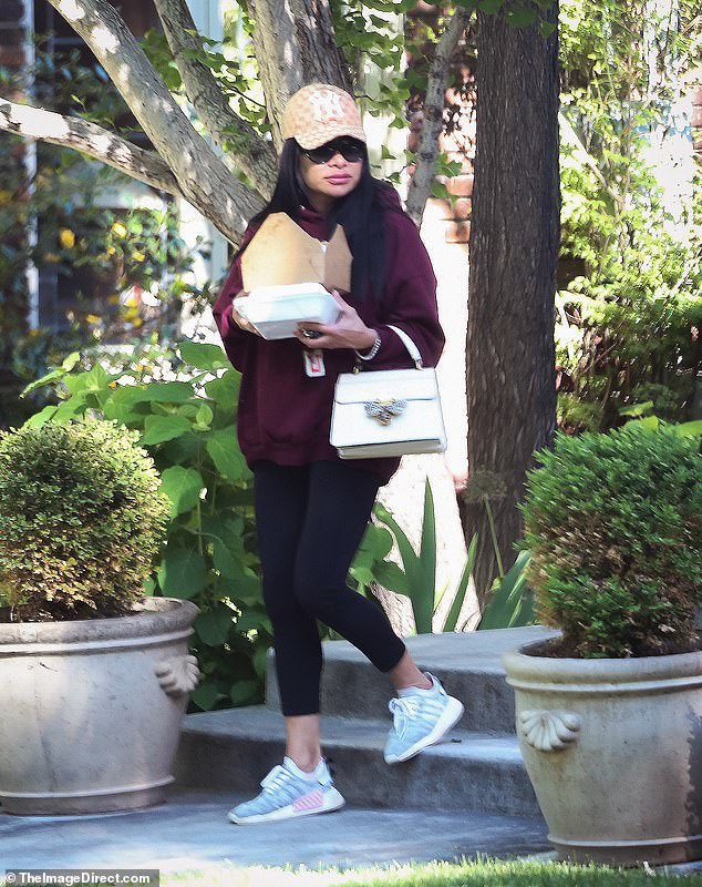Heading out: She later laced up a pair of grey Adidas sneakers and wore a New York Yankees hat as she left the house