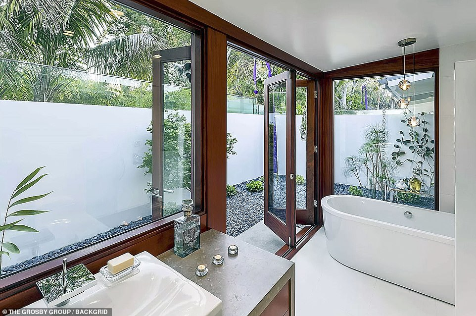 Soak it up: The master bedroom has a large soaking tub and doors opening to a small rock garden