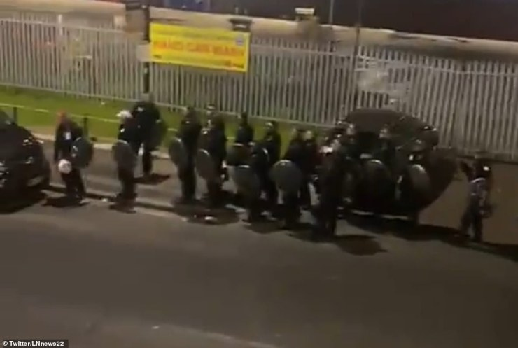 Dozens of riot police descended on south London after officers were attacked by a large group of men while attending the scene of a suspected shooting and stabbing
