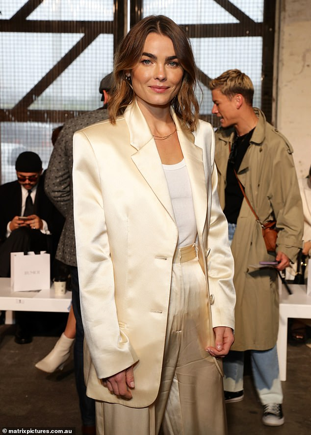 Simple and sexy:The brunette beauty wore a simple white singlet underneath the chic suit