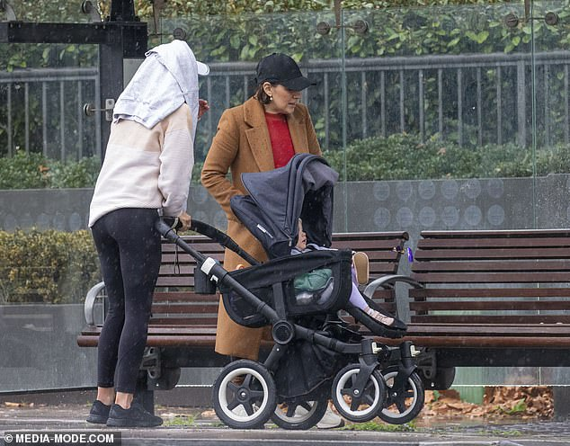 Baby on board!She wore black sneakers and wore a white cap and pushed her daughter Francesca, one, around in her pram