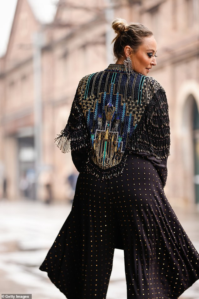 All in the detail: She then turned to reveal an elaborate pattern across her back with a mix of gold, blue and turquoise coloured beads.Beneath her jacket, the fashionista wore a beaded jumpsuit with flared legs that featured plenty of beading and splayed out as she twirled