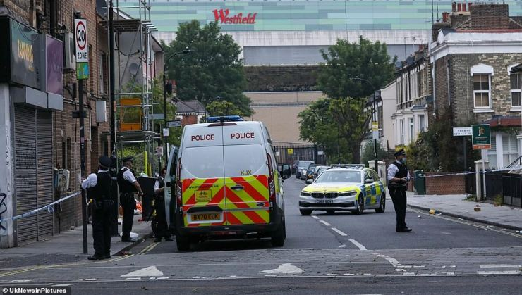 SHEPHERD'S BUSH: Police are seen by a cordon at the site of a stabbing in Shepherd's Bush yesterday