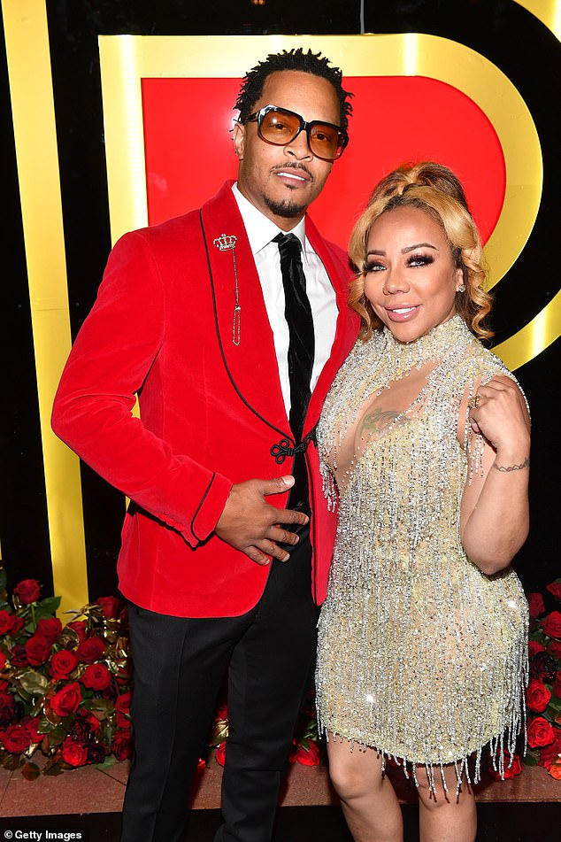 Looking good:T.I., 40, brushed aside the drama as he cut a sharp figure in a bright red blazer while posing with his glamorous wife Tiny Harris at the Fox Theater in Atlanta, Georgia, on Wednesday night