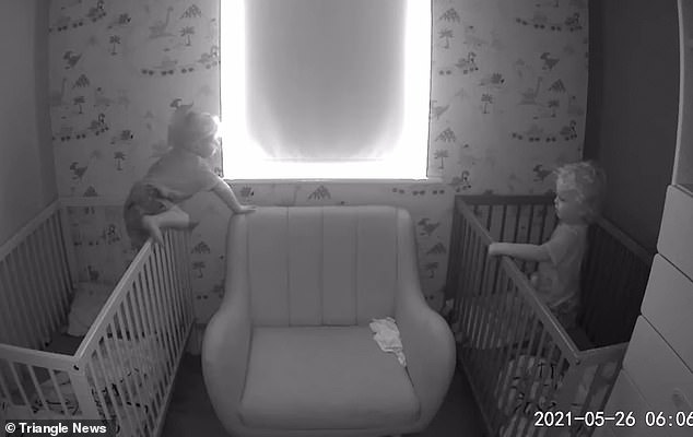 Theo climbs over the bars of his cot and makes his way over to his non-identical twin Arlo at their home in Derby