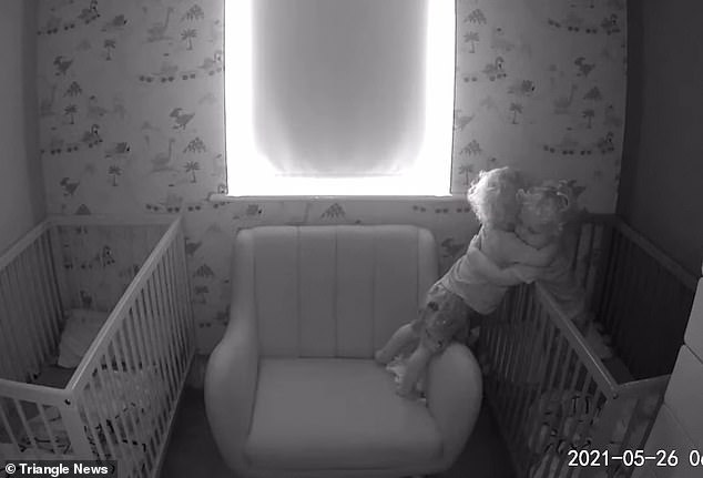 Theo stands on a feeding chair between the two cots and the twins, who are 23 months, share a warm embrace and kiss