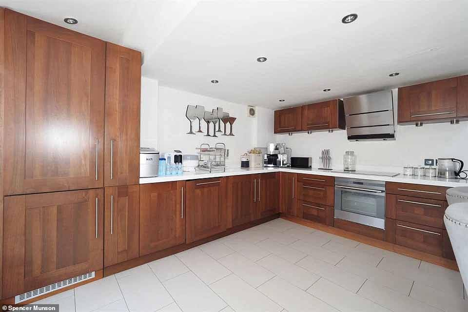 Spacious: The open-planned kitchen at her former house boasted wooden panelled cupboards, white countertops and a marble table with grey velvet seats