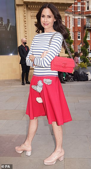 Chic: Minnie, 51, looked chic in a red skirt and striped top for the event