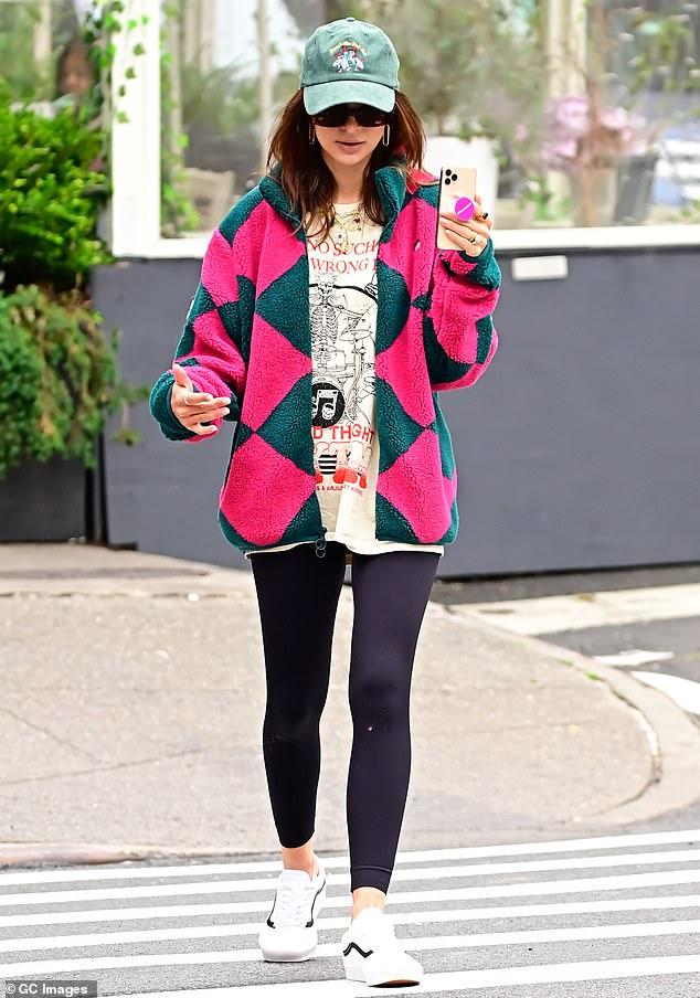 Comfy: The 29-year-old model/author bundled up in a pink and green fleece, a baggy tee shirt and snug navy leggings as she took a call on speaker phone