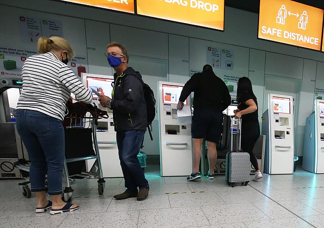 Passengers check into the North Terminal at London Gatwick Airport today before the new travel restrictions are activated