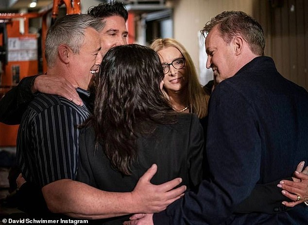 Back together: The actor followed up with a photo of the cast huddling during filming of the reunion in April