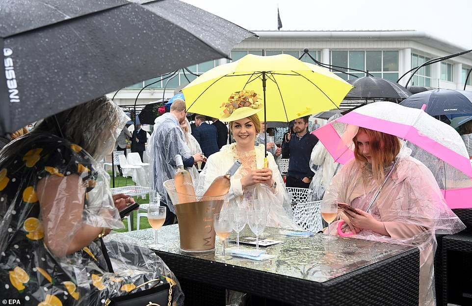 Women racegoers have a champagne under umbrellas during the Oaks day of the Derby Festival at the Epsom Downs Racecourse in Epsom