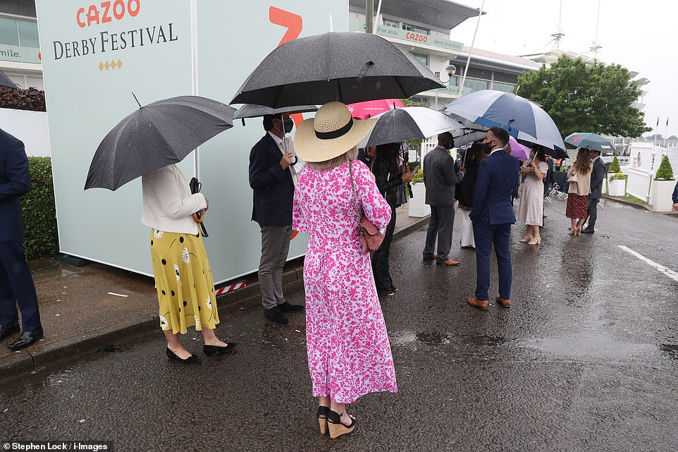 Brrr!Racegoers arriving for Ladies Day queued in the rain as they awaited to enter the enclosure for a day of festivities in the rain