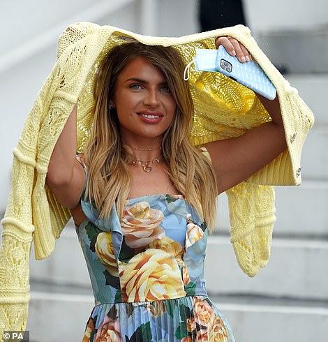 Lovely in lemon: Maria took shelter from the rain under her cardigan