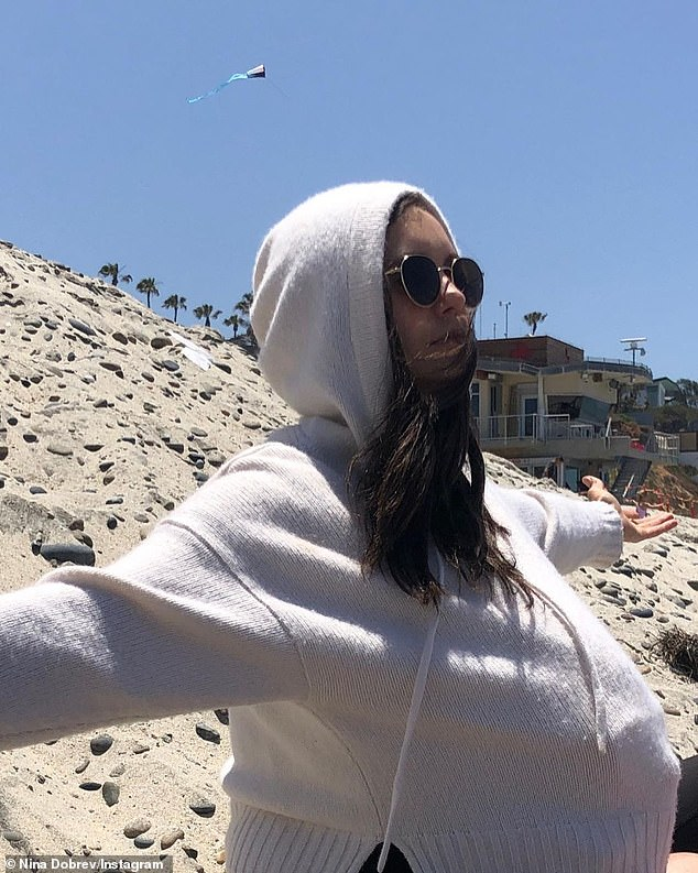 Fake out:In the first photo, Nina is seen wearing a white sweater with the hood pulled up over her head as she spreads her arms out and shows off what seems to be a pregnant belly