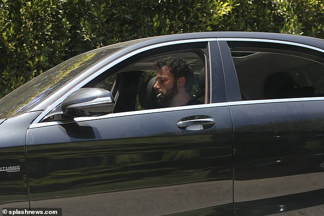 Driving and smoking:The two-time Oscar winner sported a full-grown beard and tousled hair as he glanced down whilst driving, the nearly finished cigarette hanging from his lips