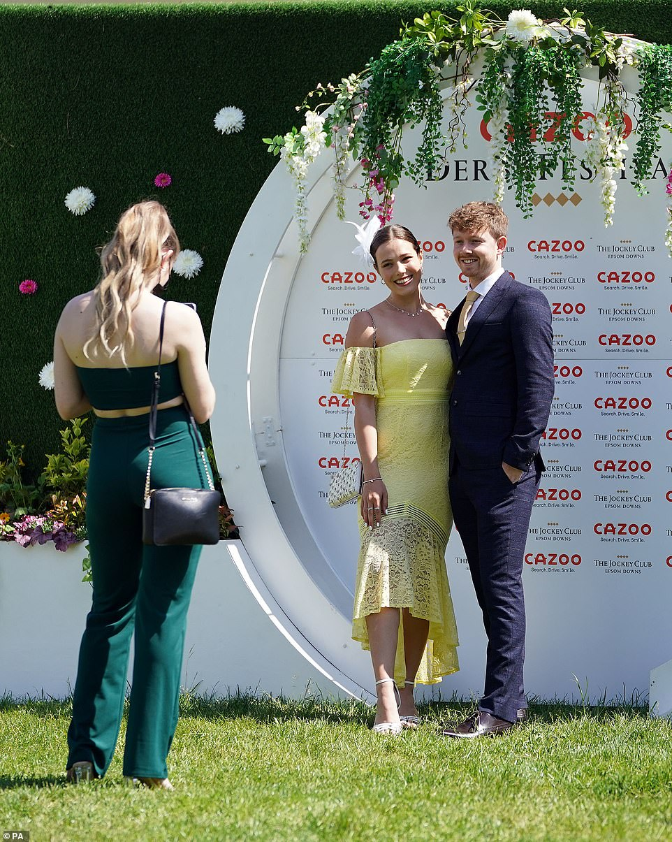 Sunny and chic: One racegoer looked stunning in a bright yellow dress as she joined a companion in a slick navy suit