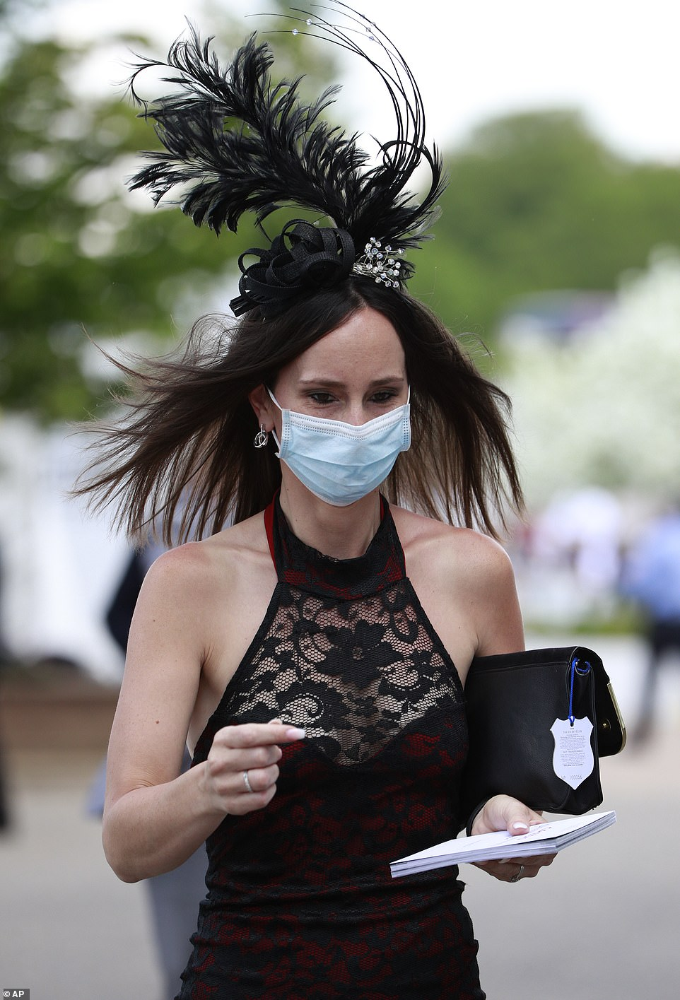 Keeping safe! One racegoer opted for a face mask and black and red lace number for her day out in Surrey