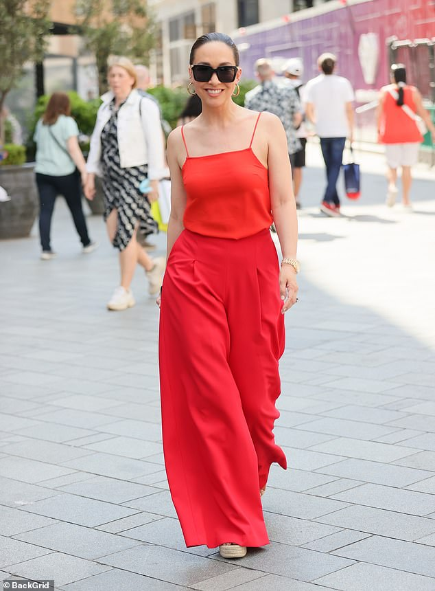 Feeling the heat: Myleene appeared to be in high spirits as she walked to work, flashing a smile for the cameras as she headed for her office