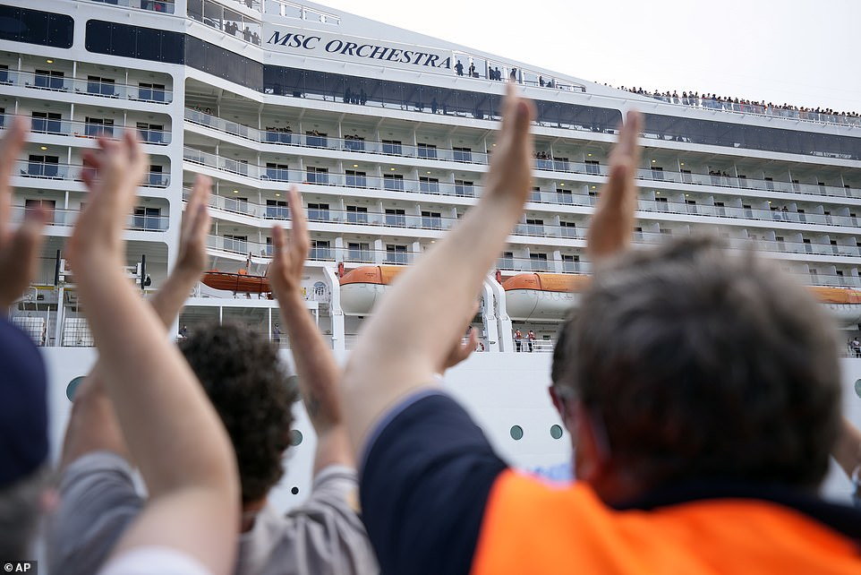 Pictured:People applaud as the 92,409-ton, 16-deck MSC Orchestra cruise ship departs from Venice, Italy, Saturday, June 5, 2021. The first cruise ship leaving Venice since the pandemic is set to depart Saturday