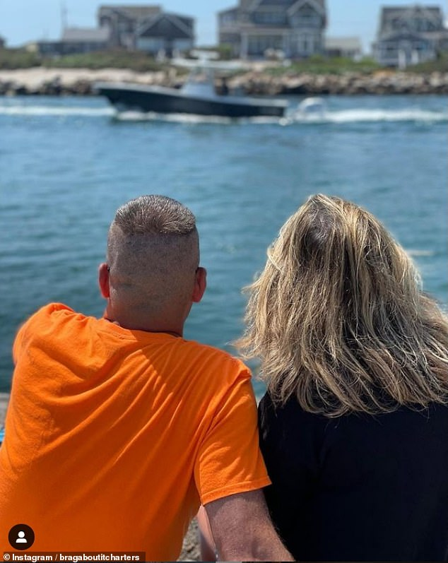Narragansett, Rhode Island: A couple watched a boat pass by Salty Brine State Beach