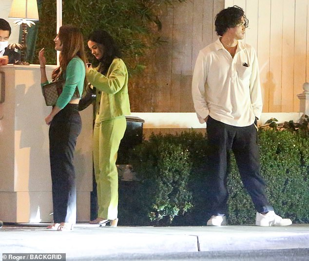 Contrast: Camila looked chic in a yellow jacket and matching slacks, while Charles wore a white long-sleeve polo shirt with black pants and white sneakers