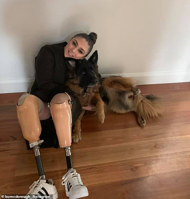 Pictured:Lauren McDonough wearing her prosthetic legs while sitting with her German shepherd, Indy