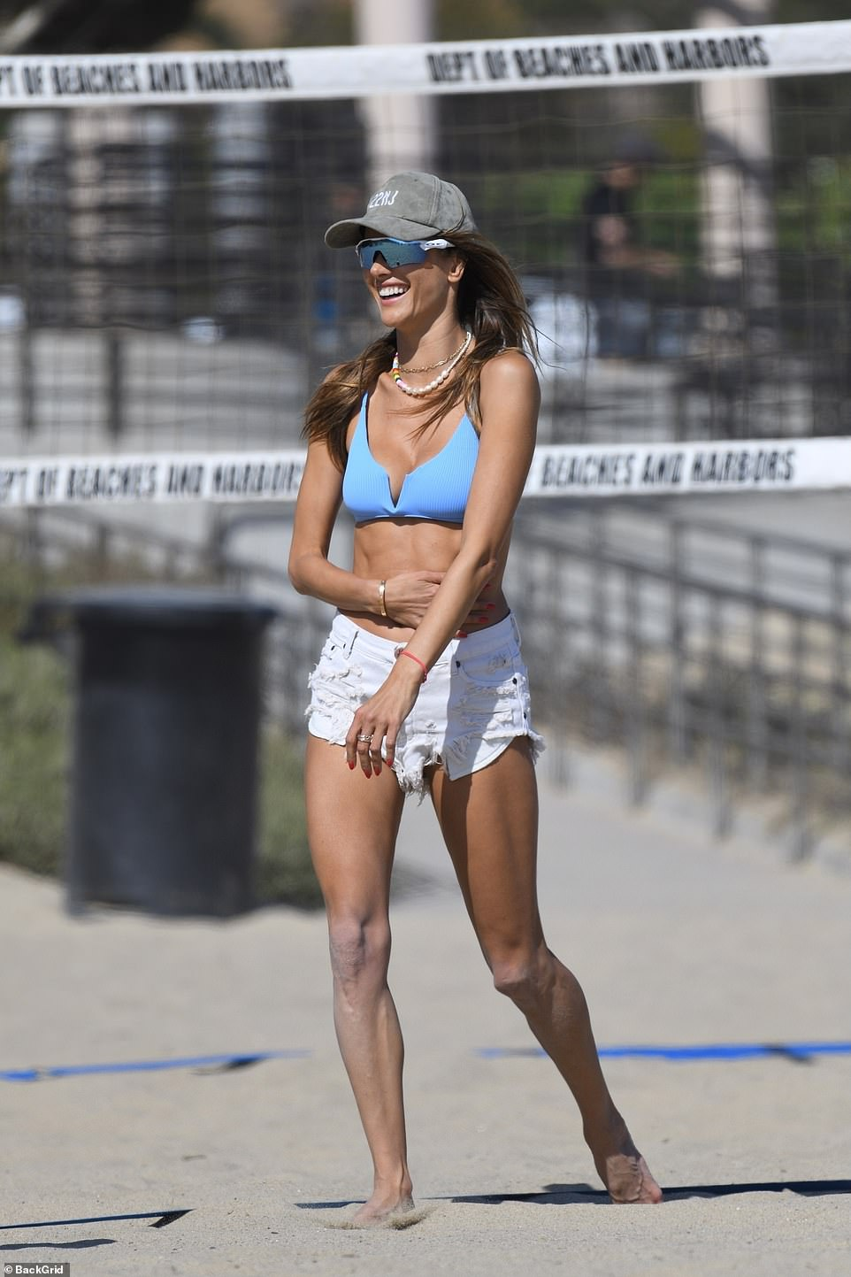 Basking in the sun: Alessandra had on wraparound Oakley-style sunglasses and a weathered gray baseball cap