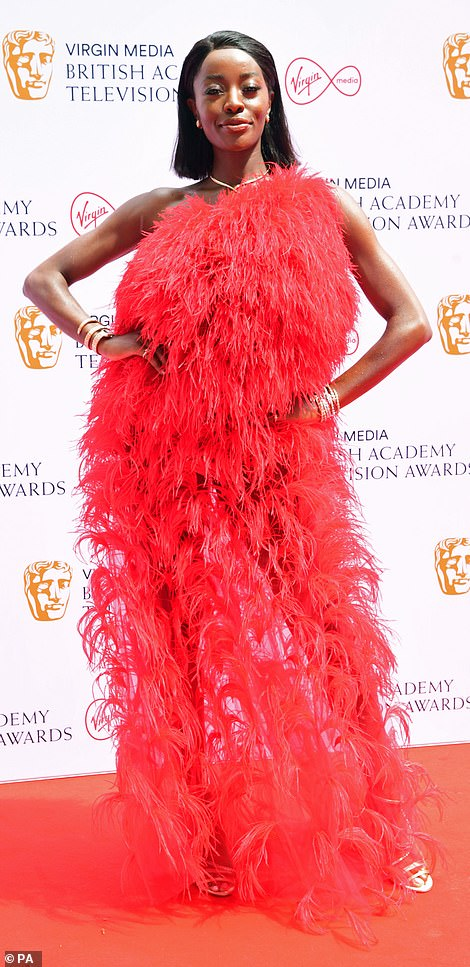 Flawless: AJ Odudu looked stunning as she stepped out on the red carpet in a red feathered one-shoulder gown at the show