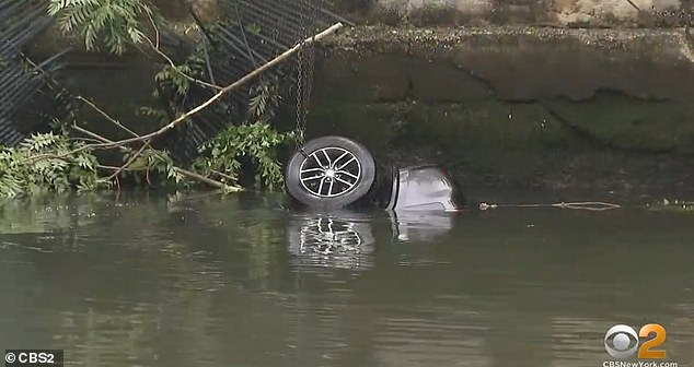 The SUV was submerged, and a local police officer who jumped into after the car couldn't get the locked door open
